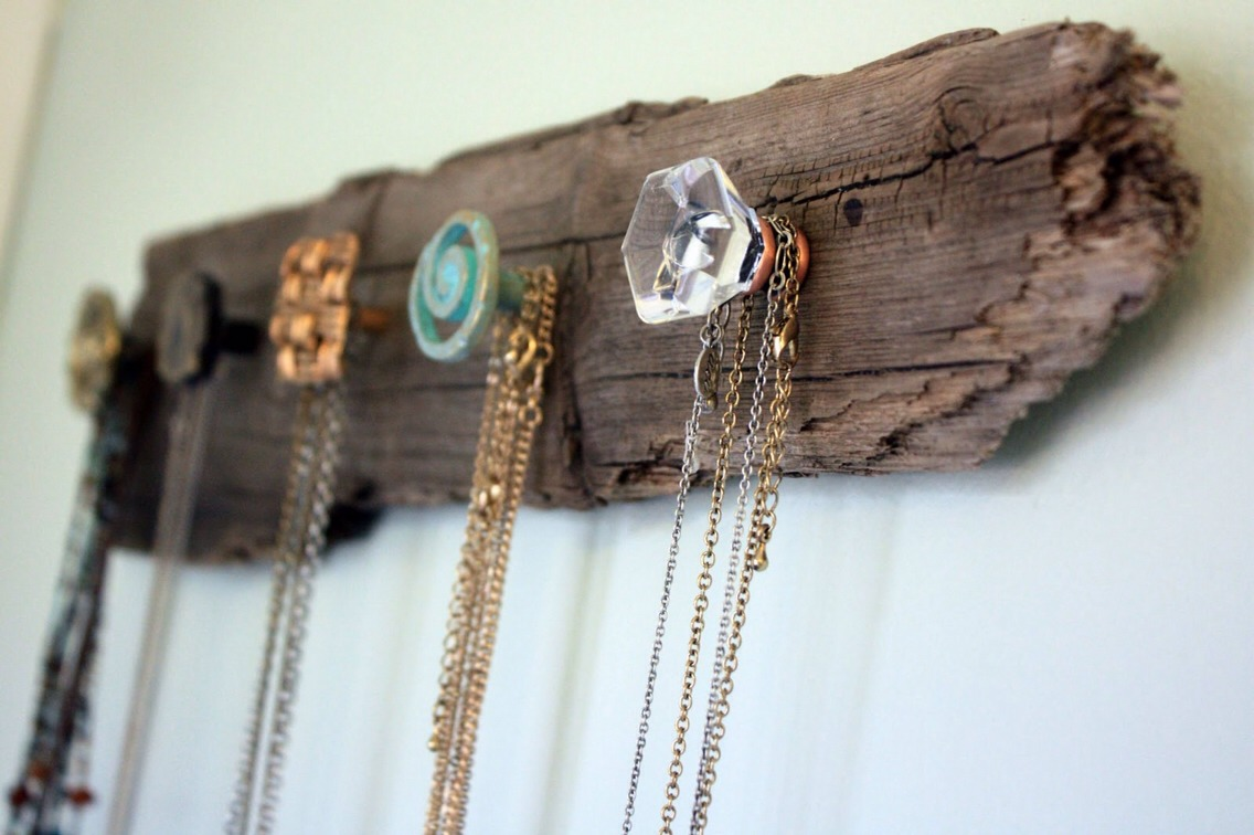 Add old dresser door knobs from vintage craft store (or google anywhere online) onto a piece of driftwood found on the beach to hang your necklaces from!