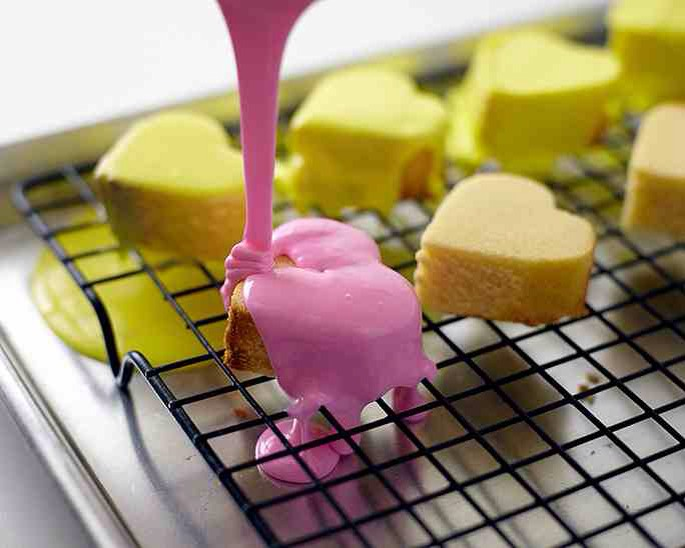 Working quickly, pour icing over the hearts, coating very generously and making sure to cover the sides.  Repeat with the remaining bowls of icing, microwaving one bowl at a time. Let hearts dry on the rack for 1 to 2 hours until the icing is very dry to the touch.