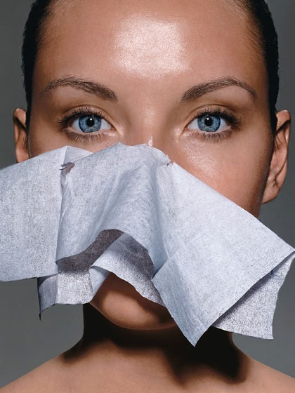 Use blotting sheets they do not take of your makeup but they do absorb oil.
