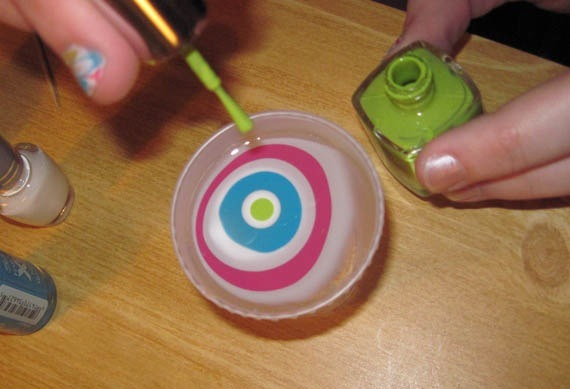 Start putting drops of nail polish onto the water of any colour and put a couple of drops of different colours