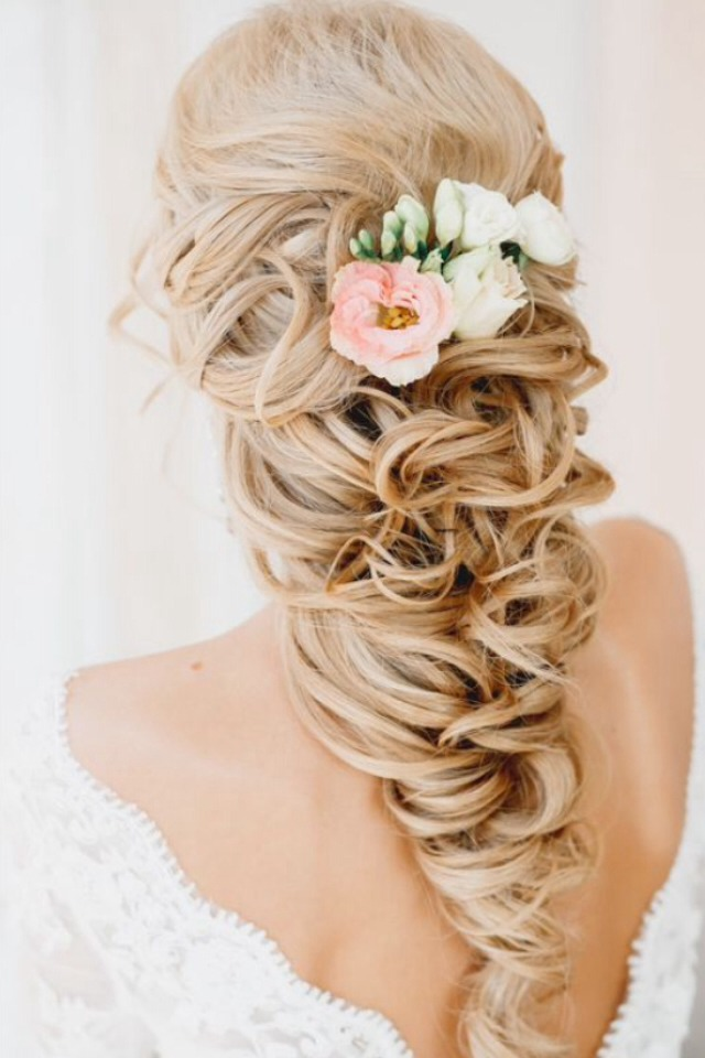 A very loose braid with curls throughout it and flowers pinned into the top.