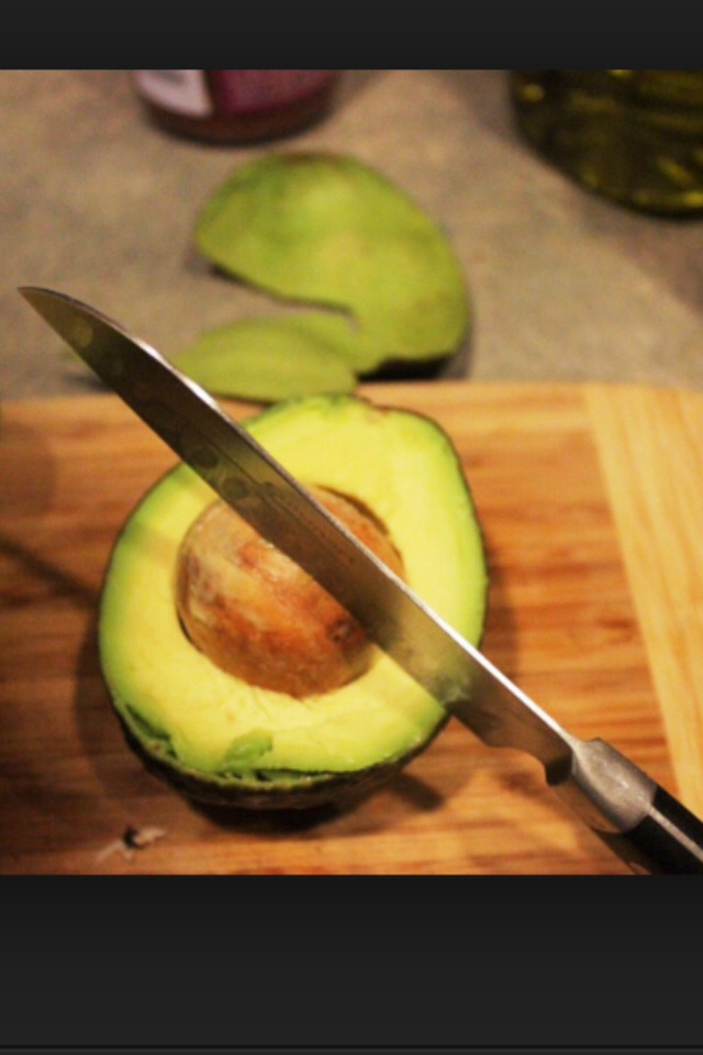 Stick the knife in the pit about half an inch deep and it will pull straight out of the avocado and stay attached to the knife.