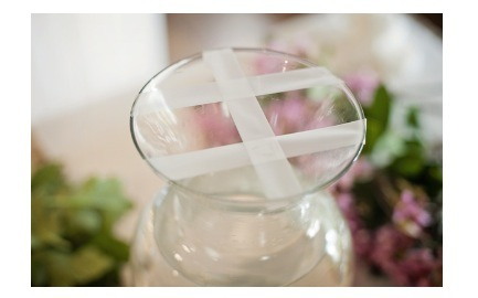 Use clear tape to hold your flowers in place bonus you can't see the tape where as floral foam can be seen through glass vases!