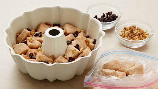 2 of 4 Separate dough into 16 biscuits; cut each into quarters. Shake in bag to coat. Arrange in pan, adding walnuts and raisins among the biscuit pieces.