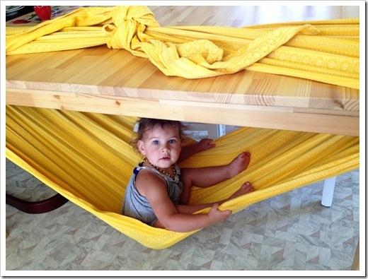 Make a hammock with a blanket tied around a table.