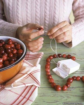 Use dental floss! Waxed dental floss is strong enough to hold your cranberries, gumdrops, popcorn and more and everything will glide on easily!