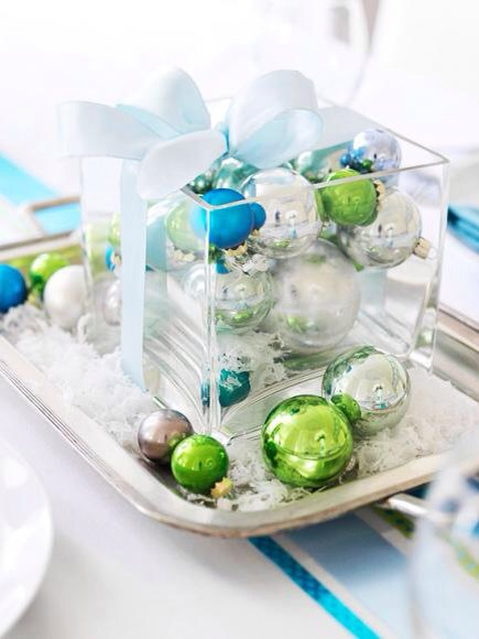 """Serve up a centerpiece  To make a showy centerpiece, place solid-color ball ornaments inside a clear-glass vase and """"serve"""" on a silver tray. Sprinkle faux snow over the display, and wrap it up with matching ribbon."""
