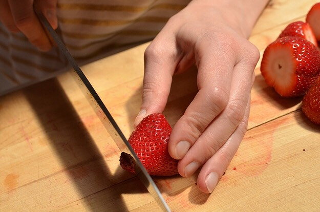 Still holding it the same way, cut off a tiny part of the strawberry's bottom tip so the berry can stand upright.