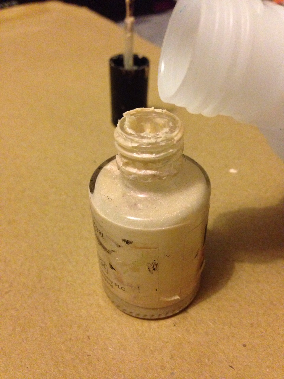 Get any nail polish remover a pour a small amount into the varnish pot, shake well.