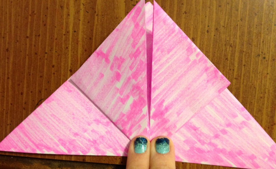 Pick up the first layer at the corner and fold it in a triangle towards the top center part of the triangle. Do it again with the other corner so it ends up looking like this.