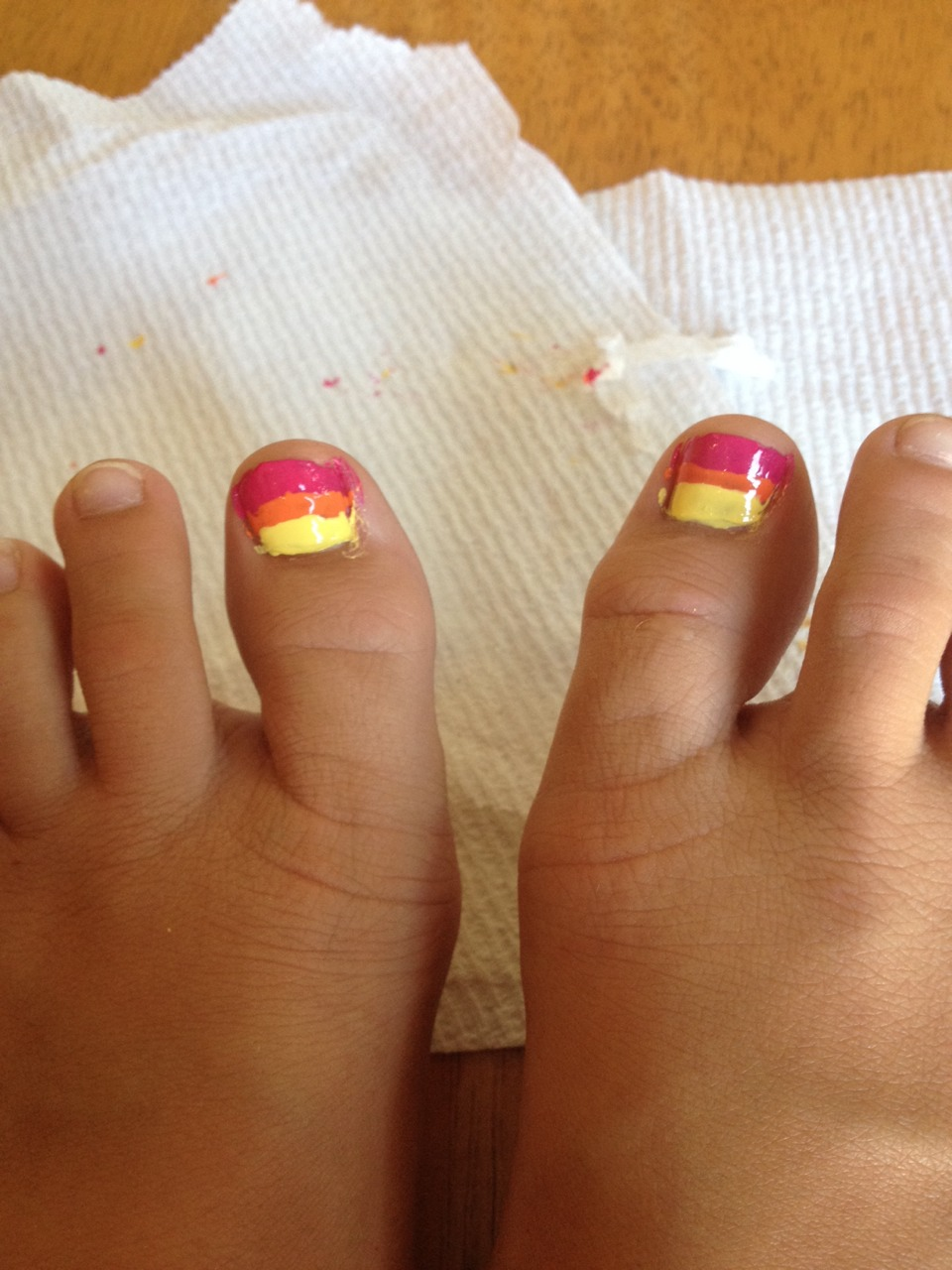 Paint your big toe in stripes using the hot pink, yellow, and orange. You can do this by using a thin brush to paint the individual stripes.