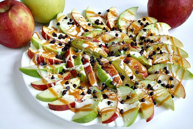 CARAMEL APPLE NACHOS  30 large marshmallows 5 Tbsp butter 35 caramels 1 Tbsp water 4-5 apples, sliced toppings (peanuts, sprinkles, mini chocolate chips, crushed candy bars, etc)  Melt the marshmallows and butter in a saucepan over low heat.  Stir periodically until completely melted and