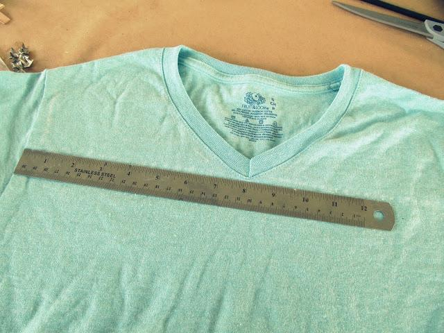 I drew a straight  line using my ruler across the front of the shirt right below the point of the V with my chalk