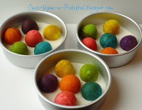 Next you get three cake pans and put your cupcake balls inside and fill with cake batter