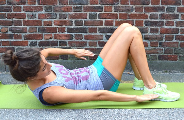 Foot tap crunches: squeeze the abs to lift your upper body from the mat and reach side to side to tap the heel of your foot, alternating back and forth for 30 seconds. Make it harder: slightly elevate your feet throughout.