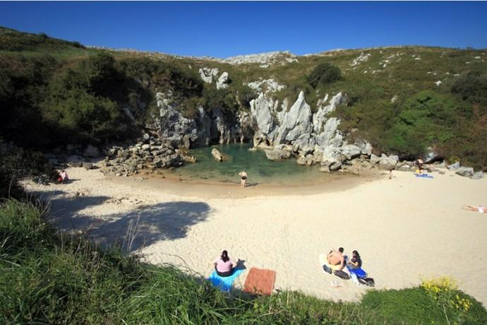 A Sandy Beach in the Middle of a Meadow This beach is located in Playa De Gulpiyuri, Llanes, Spain. It's small but it linked to underground waterways that leads to the Atlantic. Perfect for a private picnic.