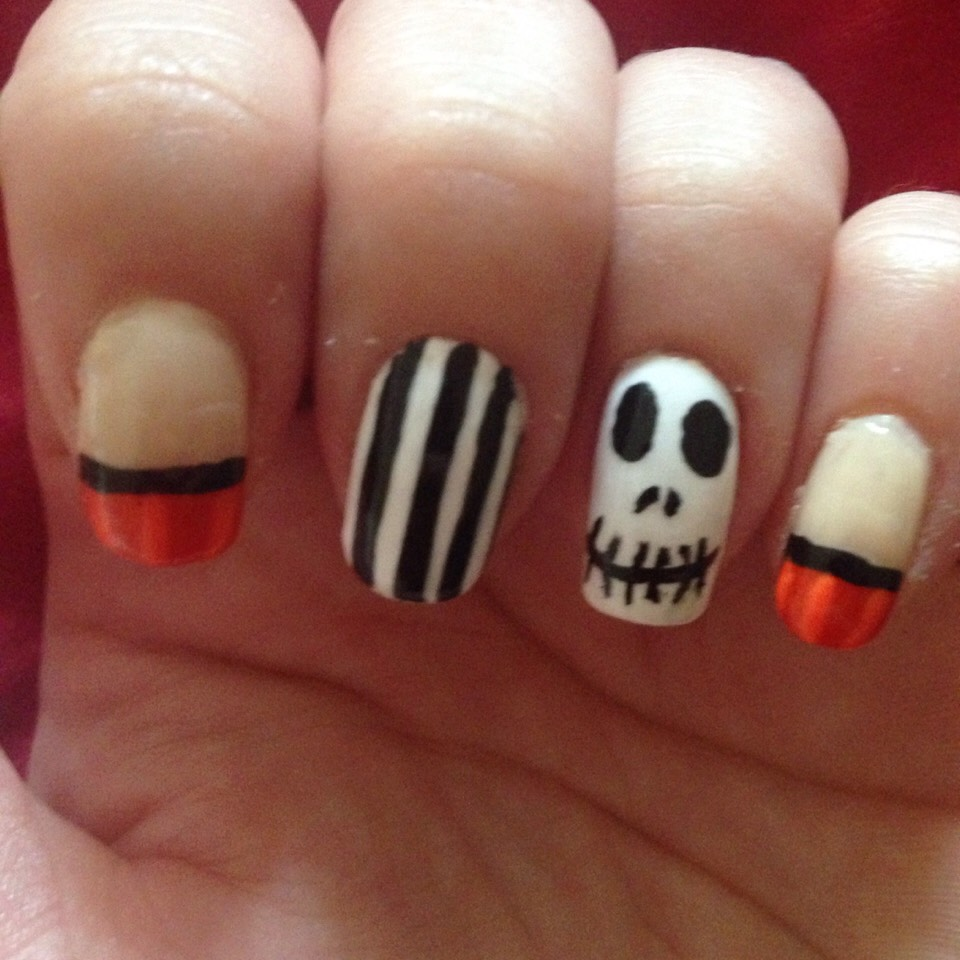 Halloween nails ; orange pumpkin tips , black and white stripes , cartoon skull