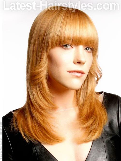 FRESH FLIP Sleek blunt cut bangs are long and extremely modern. Having the bangs round out at the temples keeps the look soft. Tons of face framing layers are chiseled fantastically to add tons of interest, flip, and fun