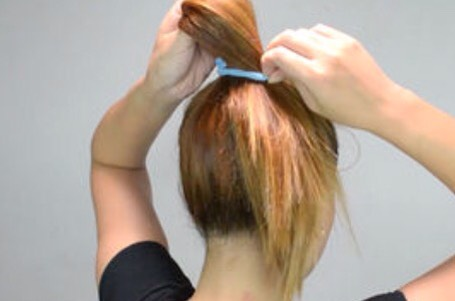 Pull your hair back. Gather your hair at the top of your head. Use an elastic band to create a ponytail, but stop halfway. If you can typically go three loops with your elastic, stop after the first one.