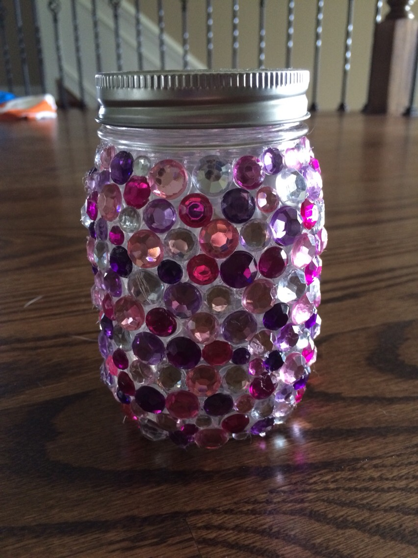 Carefully glue the gems onto the mason jar. Don't use too much glue or else it will look clumpy and bad. You can use a color scheme or just glue random colors on. I used dark and light purple, dark and light pink, and silver gems.