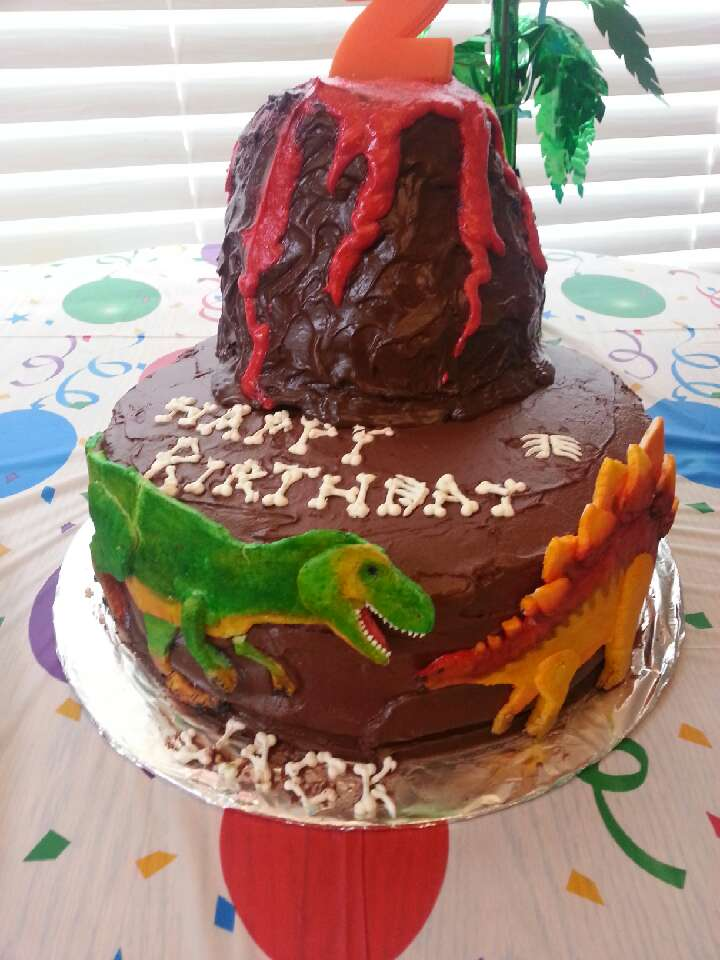 Dinosaur cake. Two tier. Chocolate buttercream frosting, fondant dinosaurs, and royal icing bones