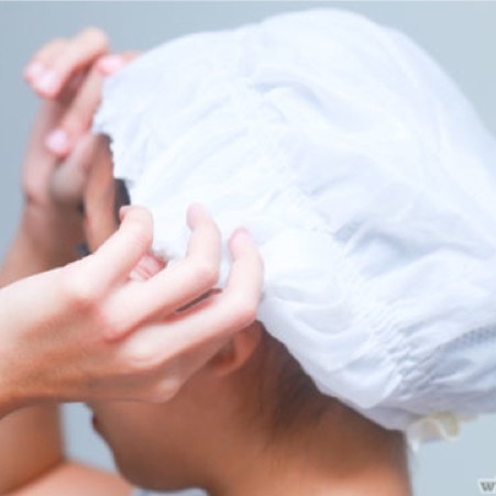 STEP 6. Put up hair into a bun and cover with a shower cap . If there are strands of hair that stick out of the cap , clip them up. You want every hair to be covered  with the shower cap.