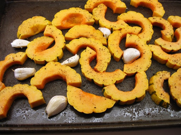 4. Put the squash and garlic cloves on a rimmed baking sheet. Drizzle with the olive oil and toss to distribute the oil. Sprinkle with salt and pepper.