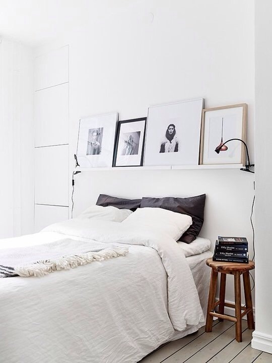 A simple picture ledge (or narrow shelf_ mounted above the bed provides a great spot for displaying art and smaller items, as seen onDecor Dots. Bonus: use clip lamps in combination with the shelf and save space on your nightstand.