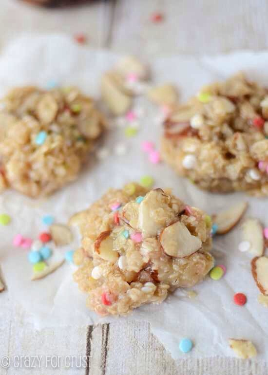 Line two cookie sheets with parchment paper. Melt butter in a medium sized saucepan over medium heat. Add sugar and creamer, stir, and cook until it just begins to bubble. Boil for 1 minute. Add extracts, almonds, and oats and cook for 1 more minute. Remove from heat and stir in sprinkles.