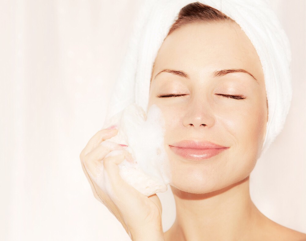 Exfoliating removes dead skin. You can buy a scrub or make your own natural scrub. Just add a cup full of sugar and several drops of coconut oil. The sugar should be brown and this will remove the dead skin  and the coconut oil will soften your skin. Coconut  oil has many benefits for your skin.