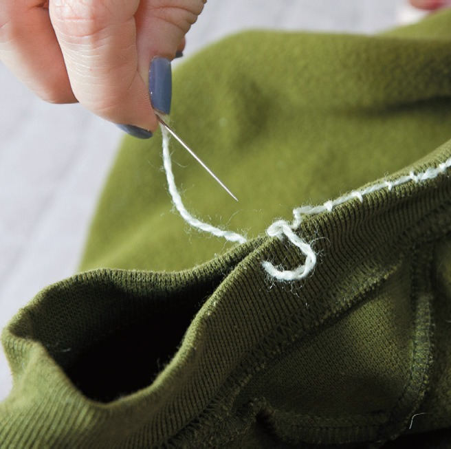 Turn your sweatshirt inside out. Gather the edges of the collar and sew them with a thread or use a sewing machine if you want it faster. Leave a small piece open.