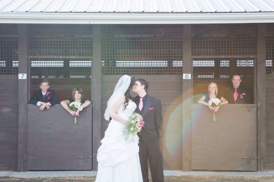 Wedding party inside of horse stables