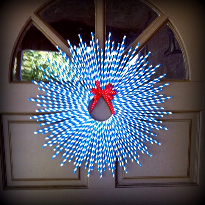 The red bow creates an interesting contrast with the blue and white plastic wreath.