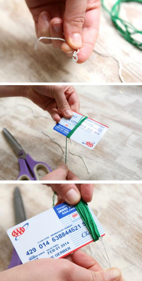 1. Take your 6-inch piece of thread and make a knot that keeps a small loop. Set aside.  2. Then wrap your emerald thread around the card as shown.  3. Feed the 6-inch piece of thread under the wrapped thread and tie a double knot. Then slide the green thread off the card.