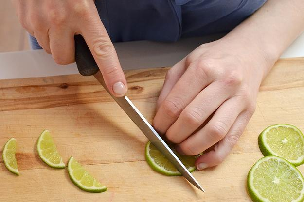 10. Slice lime (you can use the same one if you don't care about the aesthetics, or a new one if you do) into thin rounds, then cut into small wedges. You may also want to cut a small chunk through the center of each wedge's flesh so they can balance on the tip of the strawberry.