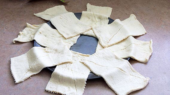 You're going to start with 2 tubes of Pillsbury Crescents. Pop them open, and arrange them in a star pattern around a 12-inch pizza pan. The dough will overlap, just make sure to leave some space in the middle for rolling them up.