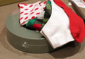 I gathered my materials: A sharp knife, a wreath form, and multi-pack socks in Christmas colors (all from the Dollar Store!).