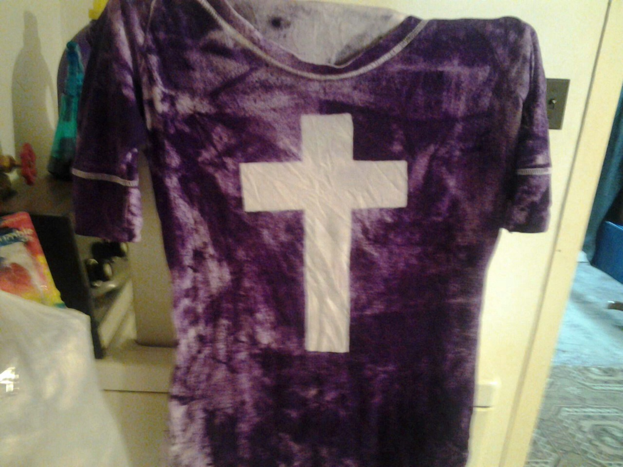 Put tape on a white shirt in the shape of a cross I used clear masking tape then put card board under the cross then mix dye in a spray bottle ( I got my spray bottles from the dollar stores) and spray then put gloves on and scrunch the fabric until u reach desired look Let sit 24 hours wash n dry