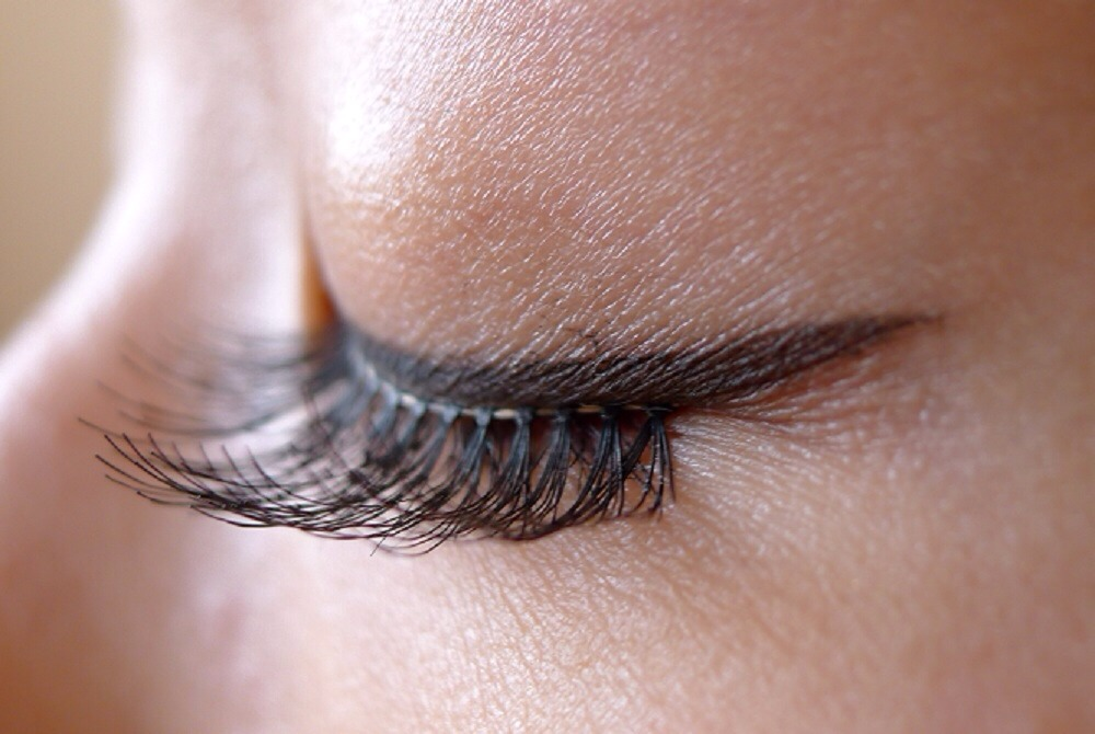 1 Remove the lashes from the pack and hold them against your eye to measure them against the length of your own natural lash line. False lashes are often too long for your eye, so ensure you cut the strips to fit.