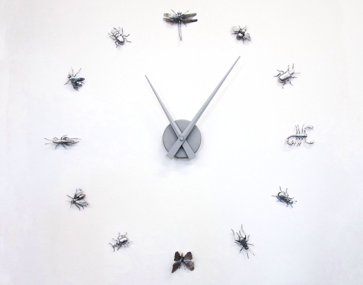 To create: Coat twelve plastic insects with silver spray paint. Once fully dried, adhere mounting tape to the back of each bug. Mount the clock dial in the desired place and stick each bug around at the correct hour.