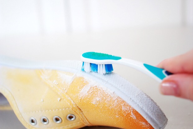 7. Once your shoes have dried, you can remove the Vaseline from the soles. Take a few teaspoons of baking powder and pour onto the Vaseline. Allow to sit for a couple of minutes and then, using an old dry toothbrush or bristled brush, scrub away at the baking powder. It should start to clump and com