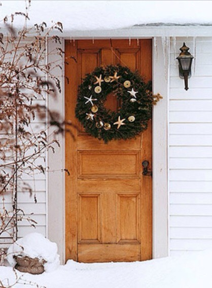 Wreaths don't have to be confined to traditional holiday themes. Use anything you love—like the gilded starfish and sand dollars displayed on this door.