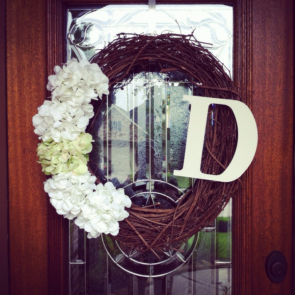 I like letter monograms for front doors. Craft store sell the giant wood letters for about  $2 and you can stain or paint them, buy the wicker wreath for $10 and add some flowers of your choice