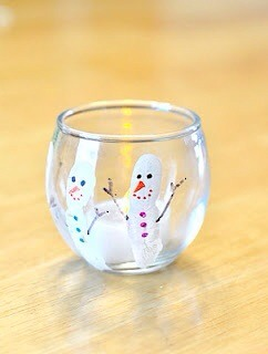 All you need is a glass votive, white paint for thumb prints(snowman) permanent markers for nose, hands, buttons, mouth and eyes.  Super cute and easy