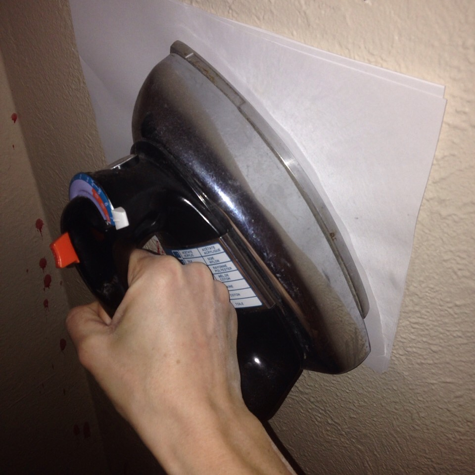 Get your iron and a stack of clean plain printer paper. Turn your iron to the hottest setting without steam. Place 2 to 3 sheets up against the waxed portion of the wall  and hold your iron to it