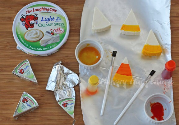 Instructions: Unwrap Laughing Cow Cheese Wedges.  Paint a stripe using yellow food coloring at the wide end of the cheese wedge.   Paint a wider orange stripe above the yellow stripe, leaving the tip white.   Allow the food coloring to dry.