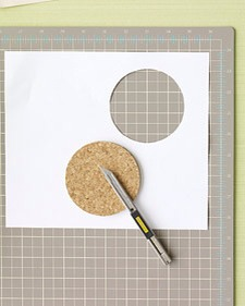 Step 1: Place map on a cutting mat, printed side down, then place cork coaster on top.  Step 2: Cut out circles from map by tracing coaster with craft knife.