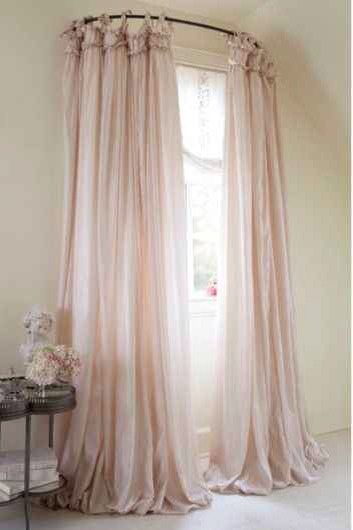 21. Use a curved shower curtain rod to make a window look bigger.