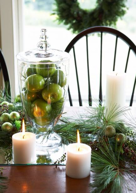 Tower of apples  Green apples are the perfect hue for an easy Christmas display. Fill a glass jar with apples; mix in loose greens for a wintry feel. Place container on a beveled edge mirror (that serves as a table runner). Fill in with additional greens, ball ornaments and candles of different size