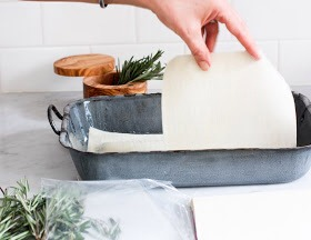 Before laying down the pasta sheets or egg roll wrappers, make sure to grease the pan and spread the bottom of the pan with some of the creamy flavorful Rosemary Béchamel sauce.